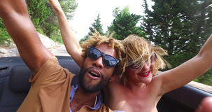 Young cheerful couple singing while driving in convertible. Young cheerful interracial couple listening to music and singing while driving in convertible car stock footage