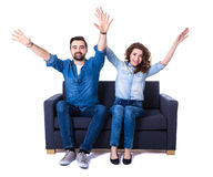 Young cheerful couple sitting on sofa and watching football isol Stock Images