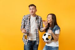 Young cheerful couple supporter, woman man, football fans cheer up support team, holding beer bottle, pizza slice. Soccer ball isolated on yellow background stock photo