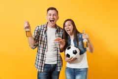 Young cheerful couple supporter, woman man, football fans cheer up support team, holding beer bottle, pizza slice. Soccer ball isolated on yellow background royalty free stock image