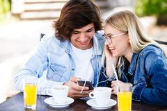 Young cheerful couple using headphones and smartphone for fun while sitting together foto de stock