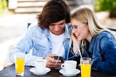 Young cheerful couple using headphones and smartphone for fun while sitting together imagem de stock