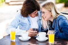 Young cheerful couple using headphones and smartphone for fun while sitting together fotografia de stock
