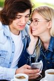 Young cheerful couple using headphones and smartphone for fun while sitting together fotografia de stock royalty free