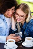 Young cheerful couple using headphones and smartphone for fun while sitting together fotos de stock royalty free