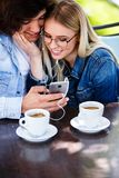 Young cheerful couple using headphones and smartphone for fun while sitting together foto de stock royalty free