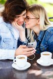 Young cheerful couple using headphones and smartphone for fun while sitting together imagens de stock royalty free