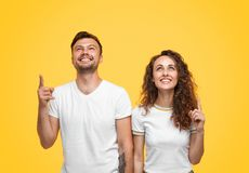 Content man and woman pointing up royalty free stock photography