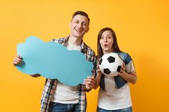 Young cheerful couple, woman man, football fans holding empty blank Say cloud, speech bubble, cheer up support team. Young cheerful couple, women man, football stock photo