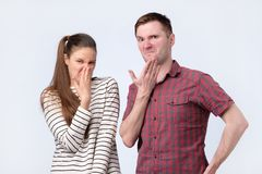 Young cheerful coupleman and woman frowning in disgust their nose from the unpleasant smell. stock images