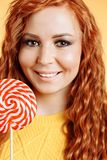 Young cheerful curly redhead woman holding a big sweet lollipop stock photography