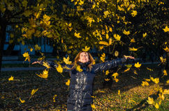 Young cheerful cute girl woman playing with fallen autumn yellow leaves in the park near the tree, laughing and smiling Royalty Free Stock Image