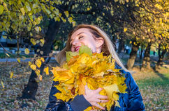 Young cheerful cute girl woman playing with fallen autumn yellow leaves in the park near the tree, laughing and smiling Royalty Free Stock Images
