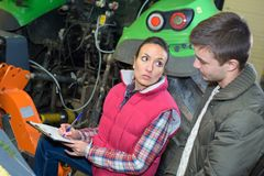 Young cheerful farming couple checking their tractor before harvest stock photos
