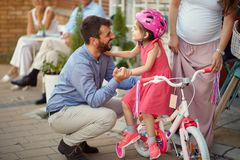 Young cheerful father buying new bicycle for little girl in bike shop. Young cheerful father buying new bicycle for happy little girl in bike shop royalty free stock images