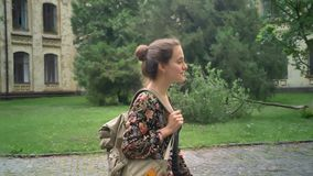 Young cheerful female college student with backpack going to college, walking on street near university, beautiful and