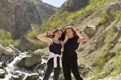 Young cheerful female friends relax together in the mountains. royalty free stock photos