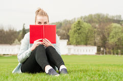 Young cheerful female hiding her face with book Stock Image