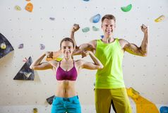 Young cheerful female and male rock climbers flexing biceps Royalty Free Stock Photo