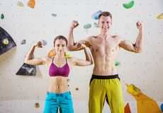 Young cheerful female and male rock climbers flexing biceps Stock Photography