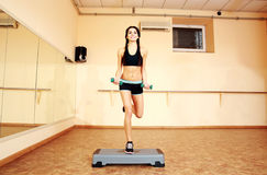 Young cheerful fit woman doing exercises with dumbells on step board Stock Image