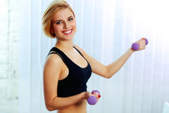 Young cheerful fit woman holding dumbbells Stock Images