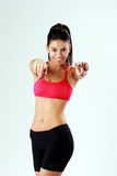 Young cheerful fit woman pointing at you Stock Images