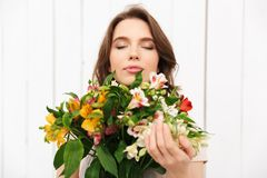 Cheerful florist woman standing with flowers. Young cheerful florist woman standing with flowers in workshop. Eyes closed Stock Photography