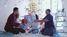 Young cheerful friends celebrating Christmas are sitting before christmas tree, holding gift boxes and having fun stock video