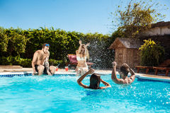 Young cheerful friends smiling, laughing, relaxing, swimming in pool. stock photo