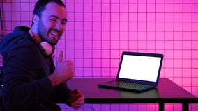 A young cheerful gamer smiling to the camera and looking at laptop. White Display. stock photography