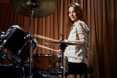 Young cheerful girl behind drums on a rehearsal Stock Photo