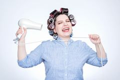 Young cheerful girl with curlers choking herself with a cord from a hairdryer. Sick of all.  royalty free stock image