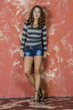 Young cheerful girl in denim shorts and a striped sweater walking in the youthful style Stock Photo