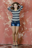Young cheerful girl in denim shorts and a striped sweater walking in the youthful style Royalty Free Stock Photos