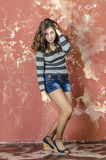 Young cheerful girl in denim shorts and a striped sweater walking in the youthful style Stock Photography
