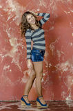 Young cheerful girl in denim shorts and a striped sweater walking in the youthful style Royalty Free Stock Photo