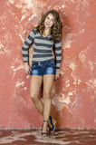 Young cheerful girl in denim shorts and a striped sweater walking in the youthful style Royalty Free Stock Image