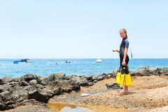 Young cheerful girl in diving suit with paddles standing on rock Royalty Free Stock Image
