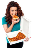 Young cheerful girl enjoying pizza alone Royalty Free Stock Photos