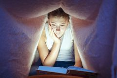 Young cheerful girl hiding under blanket and enrapt reading book royalty free stock photography