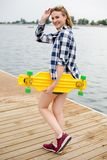 Young cheerful girl in hipster outfit holding yellow longboard in his hand and walking on a wooden pier royalty free stock photo