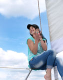 Young cheerful girl in jeans and a baseball cap. Near the sail against the blue sky stock photography