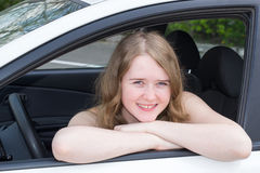 Young cheerful girl looks out of a car window Royalty Free Stock Image