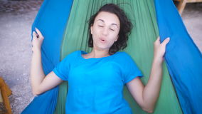 Young cheerful girl lying in hammock on tropical beach, hiding her face and laughing happily. Adorable woman in blue stock video