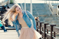 Young cheerful girl on the seashore. Young blonde walk on the promenade. Young cheerful girl on the seashore. Young blonde woman smiling Royalty Free Stock Image
