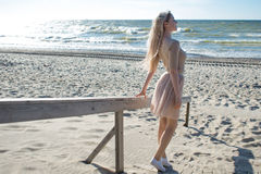 Young cheerful girl on the seashore. Young blonde woman go to the sea. Trendy beige skirt. Young cheerful girl on the seashore. Young blonde woman smiling Stock Image