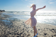 Young cheerful girl on the seashore. Young blonde woman smiling. Trendy beige skirt Royalty Free Stock Photos