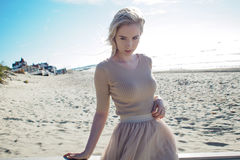 Young cheerful girl on the seashore. Young blonde woman smiling. Trendy beige skirt. Young cheerful girl on the seashore. Young blonde woman smiling Stock Photos