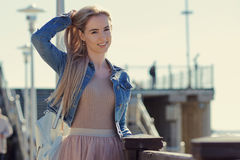 Young cheerful girl on the seashore. Young blonde woman smiling. Trendy style. Young cheerful girl on the seashore. Young blonde woman smiling Stock Photos
